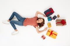 Молодая красивая курчавая девушка лежа среди подарочных коробок сняла сверху изолированный Стоковое Изображение RF