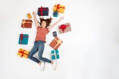 Молодая красивая курчавая девушка лежа среди подарочных коробок сняла сверху изолированный Стоковая Фотография RF