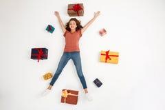 Молодая красивая курчавая девушка лежа среди подарочных коробок сняла сверху изолированный Стоковые Изображения RF