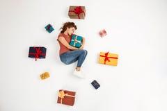 Молодая красивая курчавая девушка лежа среди подарочных коробок сняла сверху изолированный Стоковая Фотография