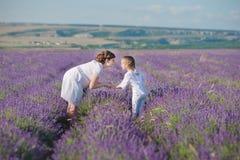 Молодая красивая мать дамы при симпатичная дочь идя на поле лаванды на день выходных в чудесных платьях и шляпах Стоковые Фото