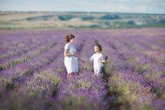 Молодая красивая мать дамы при симпатичная дочь идя на поле лаванды на день выходных в чудесных платьях и шляпах Стоковое фото RF