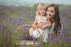 Молодая красивая мать дамы при симпатичная дочь идя на поле лаванды на день выходных в чудесных платьях и шляпах Стоковые Изображения RF