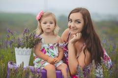 Молодая красивая мать дамы при симпатичная дочь идя на поле лаванды на день выходных в чудесных платьях и шляпах Стоковые Изображения