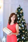 Молодая красивая милая девушка усмехаясь, стоя и держа подарок внутри Стоковые Фото