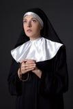 Молодая красивая монашка женщины моля с розарием над серым цветом Стоковые Изображения