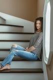 молодая красивая модель женщины с грязными длинными волосами в сорванных голубых джинсах и striped сидеть футболки крытых окном Стоковое Фото