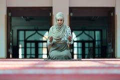 Молодая красивая мусульманская женщина моля в мечети Стоковая Фотография