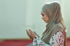 Молодая красивая мусульманская женщина моля в мечети Стоковое фото RF