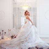 Молодая красивая невеста в роскошном платье свадьбы Огромная тучная юбка с поездом Роскошный светлый интерьер Стоковые Изображения RF