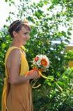 Молодая красивая невеста девушки в ярком оранжевом платье Букет лета в руках  Цветки украшения в их волосах Стоковая Фотография
