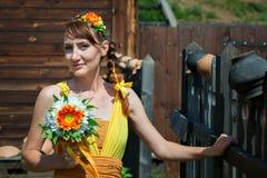 Молодая красивая невеста девушки в ярком оранжевом платье в русском деревянном доме Цветки украшения в их волосах Стоковое Изображение