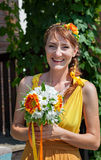 Молодая красивая невеста девушки в ярком оранжевом платье в русском деревянном доме Цветки украшения в их волосах Стоковое Изображение RF