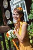 Молодая красивая невеста девушки в ярком оранжевом платье в русском деревянном доме Цветки украшения в их волосах Стоковая Фотография RF