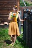 Молодая красивая невеста девушки в ярком оранжевом платье в русском деревянном доме Цветки украшения в их волосах Стоковые Фото
