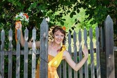 Молодая красивая невеста девушки в ярком оранжевом платье в русском деревянном доме Цветки украшения в их волосах Стоковые Изображения
