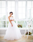 Молодая красивая невеста для того чтобы пробовать ее платье Стоковая Фотография RF