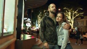 Молодая красивая пара около окна магазина узнает отношение Женщина приняла обиду на ее человека в ноче видеоматериал