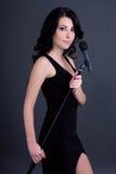 Молодая красивая певица женщины с микрофоном над серым цветом Стоковое Изображение RF