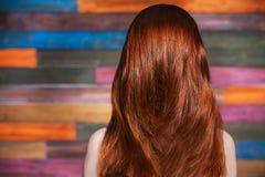 Молодая красивая рыжеволосая девушка стоя назад к камере Стоковые Фотографии RF