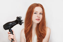 Молодая красивая рыжеволосая девушка с феном для волос в ее руке на белой предпосылке Стоковые Изображения RF