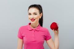 Молодая красивая сексуальная девушка с темными волосами, держа большое красное яблоко для того чтобы насладиться вкусом и dieting стоковые изображения