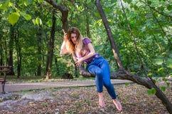 Молодая красивая сексуальная модель девушки европейского возникновения с длинными волосами в рубашке и джинсах сидя на дереве во  Стоковое Фото