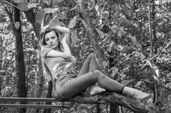 Молодая красивая сексуальная модель девушки европейского возникновения с длинными волосами в рубашке и джинсах сидя на дереве во  Стоковые Изображения RF