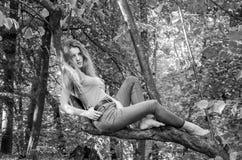 Молодая красивая сексуальная модель девушки европейского возникновения с длинными волосами в рубашке и джинсах сидя на дереве во  Стоковая Фотография