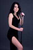 Молодая красивая сексуальная певица женщины с микрофоном над серым цветом Стоковые Фото