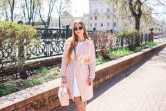 Молодая красивая стильная девушка идя и представляя в белом платье и розовом пальто в городе Внешний портрет лета молодого первок Стоковые Фото