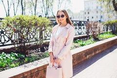 Молодая красивая стильная девушка идя и представляя в белом платье и розовом пальто в городе Внешний портрет лета молодого первок Стоковая Фотография RF