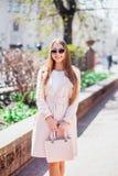Молодая красивая стильная девушка идя и представляя в белом платье и розовом пальто в городе Внешний портрет лета молодого первок Стоковое Изображение