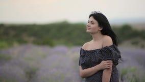 Молодая красивая темн-с волосами женщина идя и танцуя в поле лаванды видеоматериал