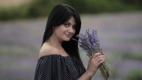 Молодая красивая темн-с волосами женщина идя и танцуя в поле лаванды сток-видео