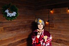 Молодая красивая темн-с волосами женщина усмехаясь в одеждах и крышке зимы с tangerines на деревянной предпосылке Стоковое фото RF