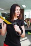 Молодая красивая тренировка женщины в спортзале используя ремни фитнеса trx Стоковое Фото
