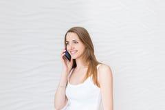 Молодая красивая усмехаясь девушка говорит сотовый телефон стоковые изображения rf