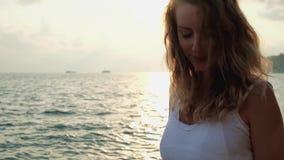 Молодая красивая усмехаясь девушка идя на пляж на заходе солнца видеоматериал