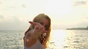 Молодая красивая усмехаясь девушка идя на пляж на заходе солнца акции видеоматериалы