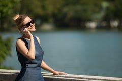 Молодая красивая усмехаясь женщина говоря на smartphone стоковые фотографии rf