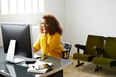Молодая красивая черная девушка работает в домашнем офисе стоковая фотография