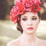 Молодая красивая японская женщина с розовыми и красными цветками Стоковые Фотографии RF