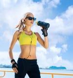 Молодая, красивая, sporty и подходящая питьевая вода девушки Стоковое Изображение