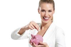 Молодая красивейшая женщина стоя с коробкой денег piggy банка Стоковые Фото