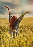 Молодая красная женщина волос стоя назад вручает до захватывающего взгляда Стоковые Изображения