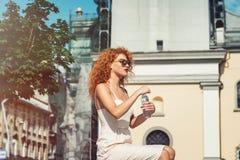 Молодая красная с волосами девушка выпивая бутылку воды Стоковое фото RF