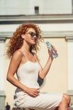 Молодая красная с волосами девушка выпивая бутылку воды Стоковые Фотографии RF