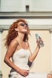 Молодая красная с волосами девушка выпивая бутылку воды Стоковая Фотография