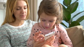 Молодая мама и ее дочь играют smartphone и усмехаются пока сидящ на софе дома движение медленное сток-видео